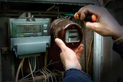 O eletricista desmonta o medidor análogo velho da eletricidade imagens de stock royalty free