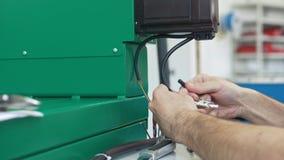 O eletricista em macacões está trabalhando com painel da energia e equipamento da maquinaria na planta video estoque