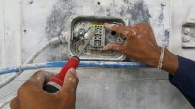 O eletricista está conectando o cabo distribuidor de corrente fotografia de stock royalty free