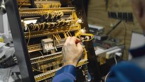 O eletricista frisa os fios e prende-os em um circuito no painel de instrumento, trabalha com alta tensão video estoque