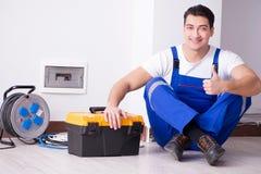 O eletricista novo que trabalha no soquete em casa foto de stock