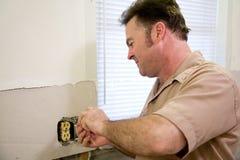 O eletricista repara a tomada Imagens de Stock Royalty Free