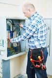 O eletricista trabalha com o verificador do medidor bonde na caixa do fusível Fotografia de Stock Royalty Free