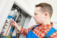O eletricista trabalha com o verificador do medidor bonde na caixa do fusível Fotografia de Stock