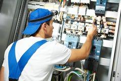 O eletricista trabalha com o verificador do medidor bonde na caixa do fusível Imagens de Stock