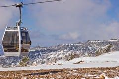 O elevador da cabine está contra montanhas Fotografia de Stock