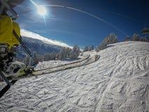 O elevador de cadeira toma-o através da área do esqui com céus azuis e inclinações brancas imagens de stock