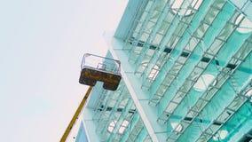 O elevador vazio da cesta para janelas e fachadas de lavagem abaixa, torre para o trabalho da alta altitude no estádio filme