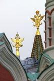 O emblema nacional de águias douradas de Rússia na torre repica Imagens de Stock