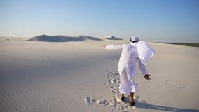 O emirado masculino novo alegre do xeique dos UAE do Arabian exulta na vida e anda com as extensões do deserto na noite clara filme