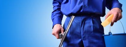 O empregado da limpeza de janela com trabalho utiliza ferramentas o fundo azul foto de stock royalty free