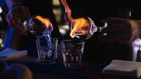 O empregado de bar ajusta o fogo a um cocktail ardente na barra filme