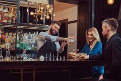 O empregado de bar brutal à moda alegre serve um par atrativo que passe uma noite em uma data imagens de stock royalty free