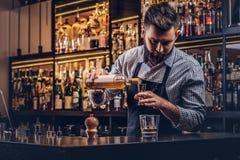 O empregado de bar brutal à moda em uma camisa e em um avental faz um cocktail na barra opor o fundo fotografia de stock