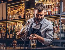 O empregado de bar brutal à moda em uma camisa e em um avental faz um cocktail na barra opor o fundo fotos de stock