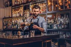 O empregado de bar brutal à moda em uma camisa e em um avental faz um cocktail na barra opor o fundo imagens de stock
