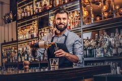 O empregado de bar brutal à moda em uma camisa e em um avental faz um cocktail na barra opor o fundo imagens de stock royalty free