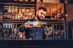 O empregado de bar brutal à moda em uma camisa preta faz um cocktail na barra opor o fundo imagens de stock royalty free