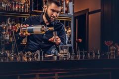 O empregado de bar brutal à moda em uma camisa preta faz um cocktail na barra opor o fundo imagens de stock