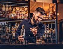 O empregado de bar brutal à moda em uma camisa preta faz um cocktail na barra opor o fundo foto de stock royalty free