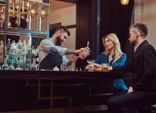 O empregado de bar brutal à moda serve um par atrativo que passe uma noite em uma data fotografia de stock