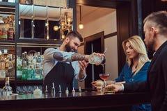 O empregado de bar brutal à moda serve um par atrativo que passe uma noite em uma data imagem de stock royalty free