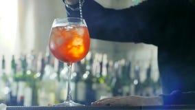 O empregado de bar com a colher longa do metal nos braços mistura o cocktail colorido com o gelo e o uísque no vidro na mesa video estoque