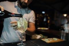 O empregado de bar derrama o champanhe de uma garrafa em um vidro em um clube noturno na barra Empregado de bar profissional que  imagem de stock