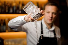 O empregado de bar derrama o cocktail alcoólico com gelo usando o filtro e os glas fotografia de stock