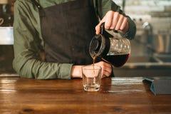 O empregado de bar derrama o café em um vidro Imagens de Stock
