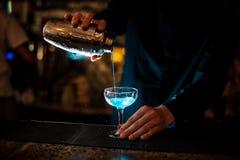 O empregado de bar derrama de um abanador em um vidro da lagoa do azul do cocktail do álcool imagens de stock