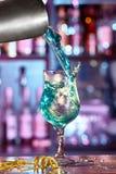 O empregado de bar derrama um cocktail azul da lagoa de um abanador em um bea imagens de stock