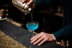 O empregado de bar derrama uma lagoa azul do cocktail do álcool no vidro imagem de stock