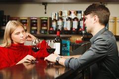 O empregado de bar e o menina-visitante bebem e falam sobre o vinho Imagem de Stock