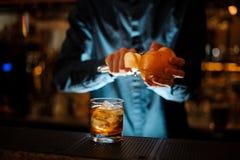 O empregado de bar em uma camisa azul termina preparar um cocktail alcoólico antiquado imagens de stock royalty free