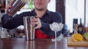O empregado de bar está agitando o cocktail em uma barra no dia, usando dois copos do metal filme