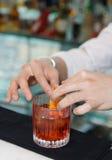 O empregado de bar está decorando a bebida com entusiasmo de limão Fotos de Stock Royalty Free