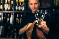 O empregado de bar está limpando o vidro com um pano no fundo do contador da barra O barman que limpa o vidro na barra imagem de stock