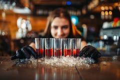O empregado de bar fêmea nas luvas põe bebidas sobre o gelo imagens de stock royalty free