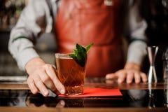 O empregado de bar guarda um cocktail com a hortelã em sua mão fotos de stock