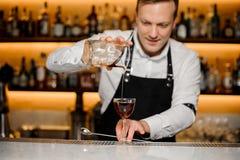 O empregado de bar no bar derrama o uísque frio no cálice fotografia de stock