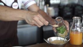 O empregado de bar põe sobre o cocktail da tabela A com cal e hortelã no vidro filme