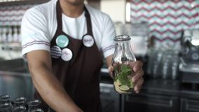 O empregado de bar põe sobre o cocktail da tabela A com cal e hortelã no vidro video estoque