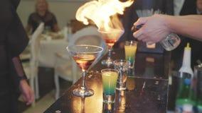 O empregado de bar prepara um cocktail e ajusta-o no fogo vídeos de arquivo
