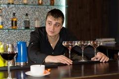 O empregado de bar que olha acima como alguém pede a atenção imagem de stock royalty free
