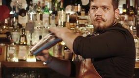 O empregado de bar sério com bigode engraçado está agitando bacias do metal com cocktail filme