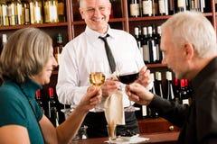O empregado de bar sênior dos pares da barra de vinho derrama o vidro Foto de Stock Royalty Free