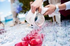 O empregado de mesa derrama o suco da cereja Imagem de Stock Royalty Free