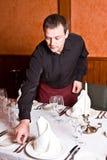 O empregado de mesa masculino arranja pratos na tabela mim fotos de stock royalty free