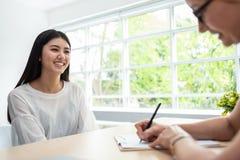 O empregado do sexo feminino asiático seguro está sorrindo durante o interv do trabalho imagem de stock